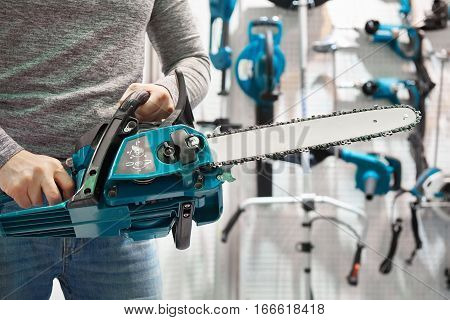 Chain Saw In Hands At Store
