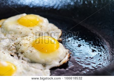 Fried eggs in a frying pan. Process of cooking eggs closeup. Food Background