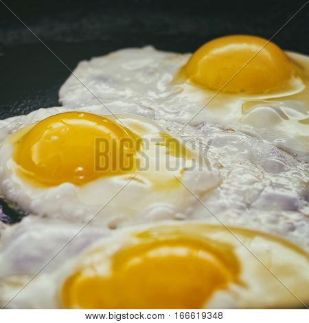 Vintage photo of Fried eggs in a frying pan. Process of cooking eggs closeup. Food Background