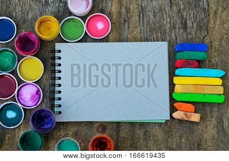 Set of gouache paints and a sketch book for drawing artistic tools on old wooden background. Tools for creative work. Concept of back to school and creative art. Top view. Copy space.