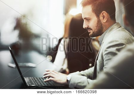 Programmer working and developing software in office on laptop