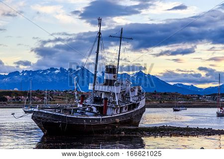 Old broken ship stranded ashore and village with mountains in the background Ushuaia Patagonia Argentina