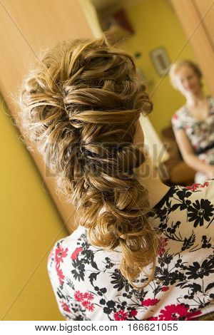 Close-up hairdresser coiffeur makes hairstyle. Beauty and Fashion