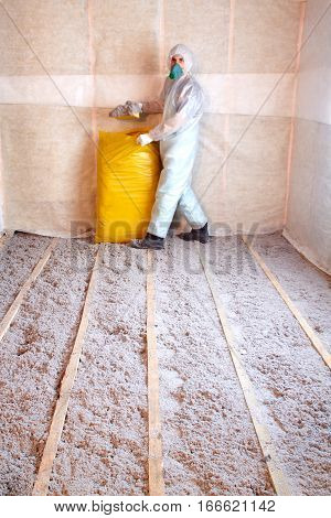 Master stacked cellulose insulation in the floor, Insulated floor, a warm home, eco-friendly insulation, insulation paper, builder at work