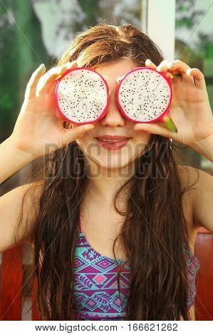 girl with dragon fruit circles on swimming pool background