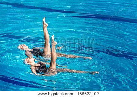 Synchronized swimming pair, toned image, blue background