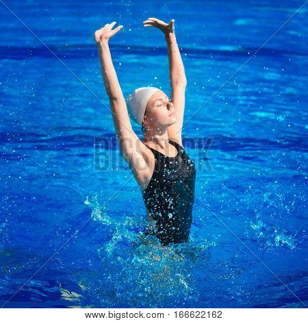 Single synchronized swimmer, toned image, blue background