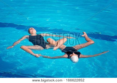 Synchronized swimmers performing, toned image, blue background