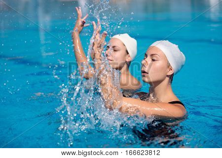 Synchronized swimming duet, toned image, blue background