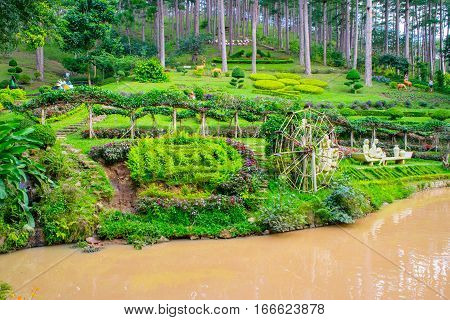 Landscape design of relax tropical garden with statues on a river side, Dalat city, park Prenn, Vietnam, October 2016