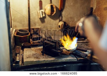 Goldsmith melting metal to liquid state industry
