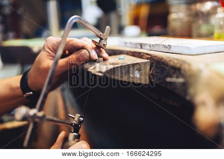 Jeweler using saw to create jewelry at shop