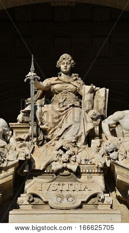 Goddess of Justice marble statue on throne with sword and book in front of old Palace of Justice in Rome