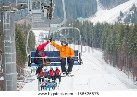 Skier And Snowboarder Riding Up On Ski Lift