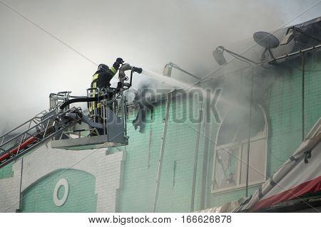 Firefighters in action fighting fire in smoke.