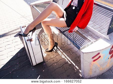 woman traveling keeping luggage at train platform