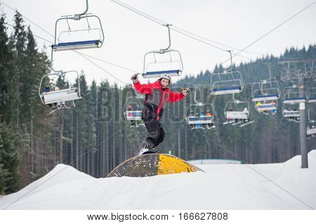 Snowboarder Flying Over A Hurdle In Winter Day