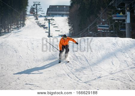 Skier Skiing Downhill After Jumping At Ski Resort