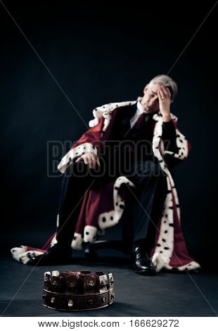 businessman in king's clothes lost it and looks quite depressed