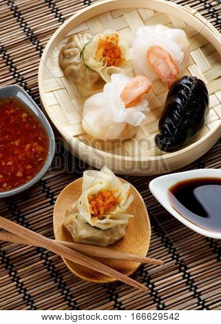 Assorted Dim Sum in Bamboo Steamed Bowl and Tori with Chiken on Wooden Plate with Red Chili and Soy Sauces and Chopsticks closeup on Straw Mat background