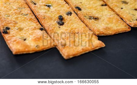 Sweet cookies with raisins. Pastry strips on black background.
