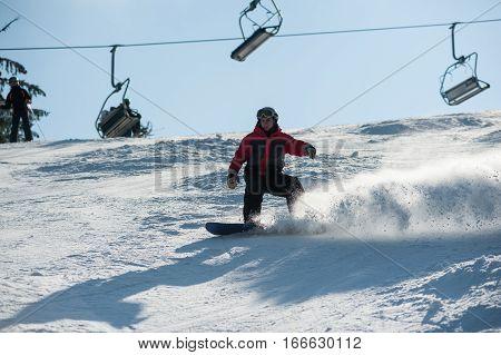 Man Boarder Riding Downhill At Ski Resort Against Ski-lift