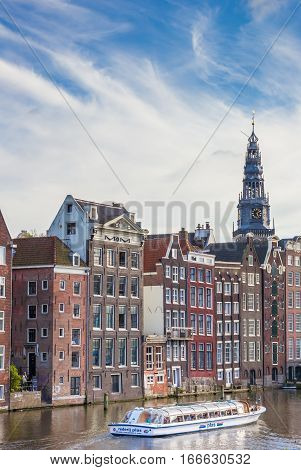 AMSTERDAM, NETHERLANDS - SEPTEMBER 18, 2016: Traditional houses and a cruiseboat at the Damrak in Amsterdam, Holland