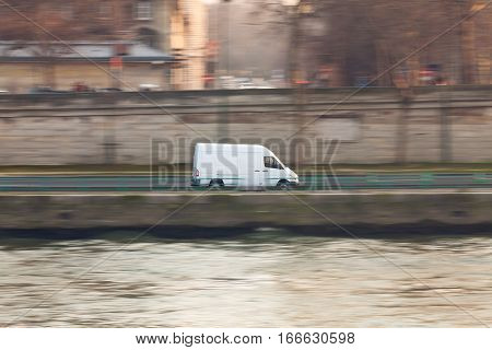 white delivery van driving through the streets of paris. the van is sharp, rest is motion blurred.