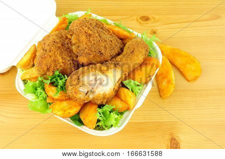 Southern fried chicken portions in a take away box on a wood background