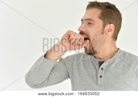 Portrait of a young man yawing, tired