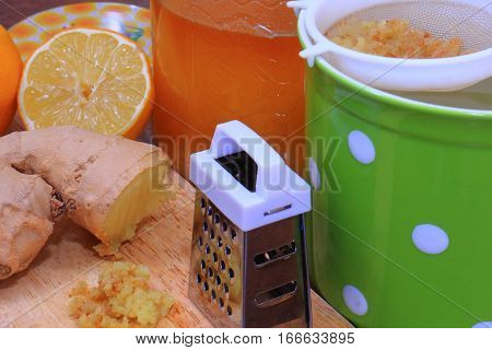Preparing ginger tea mug in green with white polka dots with lemon and honey