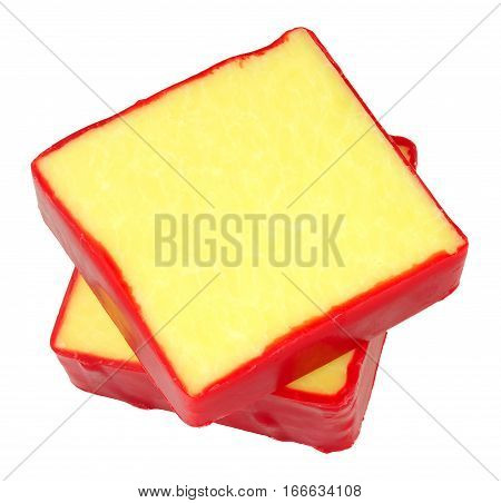 Monterey Jack cheese squares with red wax coating isolated on a white background