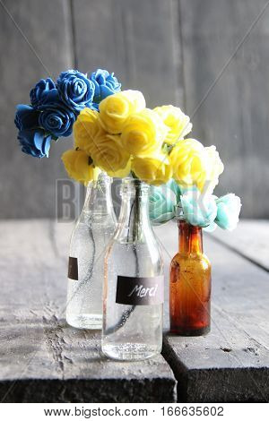 nice flowers in the bottles and label Merci, vintage style