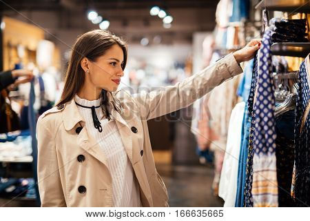 Beautiful brunette woman choosing and buying clothes