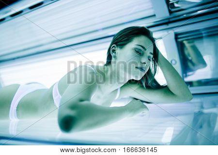 Beautiful sexy cute brunette sunbathing in solarium