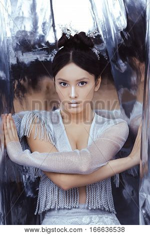 Portrait of futuristic young woman. Reflection of our mind and soul concept. Beautiful young multi-racial asian caucasian model cyber girl in silver urban clothes with conceptual hairstyle and make-up in metallik silver capsule.