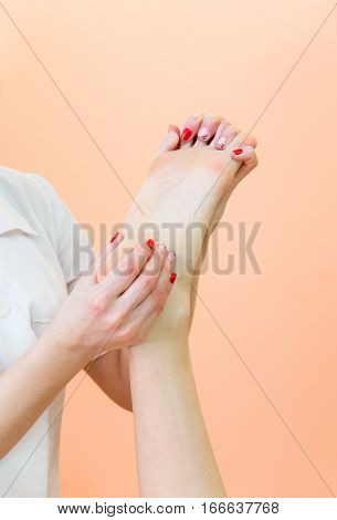 Masseur kneads the foot client. Wellness and relaxation massage.