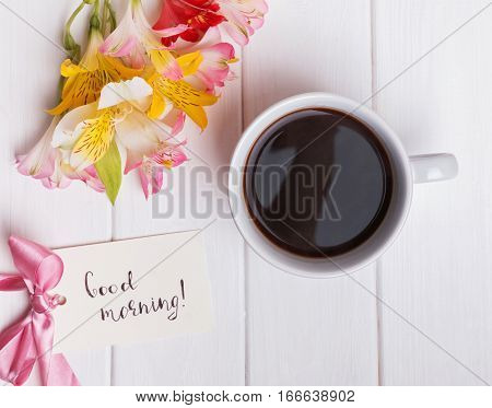 Alstromeria flowers and coffee on the white table, top view.