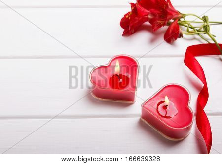 Two heart shaped candles, ribbon and red flowers on the white table, close-up