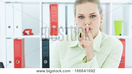 Portrait of an attractive business woman with finger on lips. Young businesswoman in office asking for silence. Woman with finger on lips gesturing for quite.