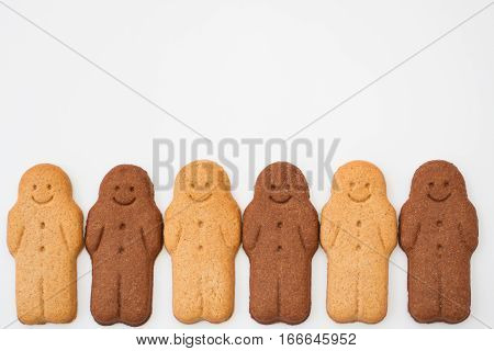 A row of happy and smiling, black and white gingerbread men on an isolated background representing racial harmony, diversity and equality.