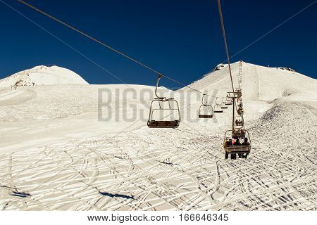 Photo of the Chairlift closeup with ski run in bright sunny winter day. Freeride trails. Blue sky and white snow. Skiing resort. Extreme sport. Active holiday. Free pastime concept. Copy space.