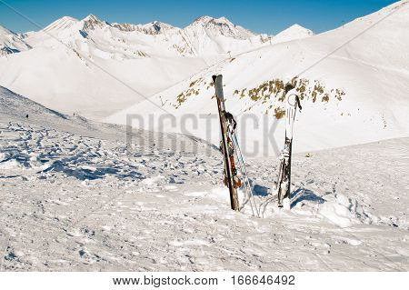 Photo of the Pair skis in snow. Skiing, winter season. Mountain landscape. Extreme sport. Active lifestyle. Danger concept. Tourism industry. Negative space.