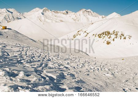 Photo of the Ski slope and freeride traces at skiing resort. Mountain range and hills on background. Extreme sport. Active lifestyle. Danger concept. Tourism industry. Negative space.