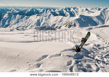 Photo of the Snowboard in snow. Skiing resort, winter season. Mountain landscape. Extreme sport. Active lifestyle. Danger concept. Tourism industry. Copy space.