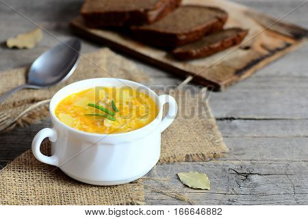 Delicious rice soup with chicken, potatoes, green onions and carrots in a bowl. Bread slices, burlap textile, spoon on wooden table. Light soup recipe. Closeup