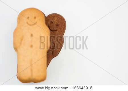 Black and white, happy and smiling gingerbread men having fun and playing peek a boo on an isolated, white background.