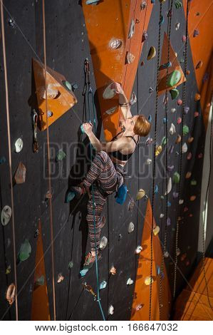Female Climber Is Climbing Up On Indoor Rock-climbing Wall
