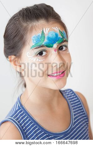 Smiling brunette girl face painted with blue flower on her face