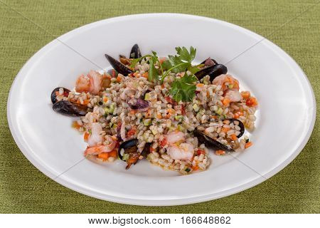 barley risotto with seafood and vegetables on white plate